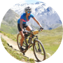 A man wearing a helmet and sports clothes is riding a bicycle in the mountans
