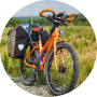An orange touring bike is standing in the meadow